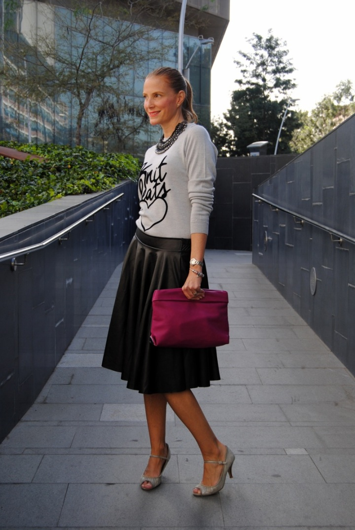 Black leather skirt and pink clutch