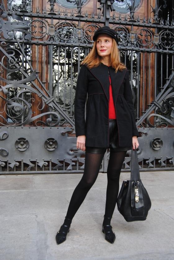 Look con abrigo negro, suéter rojo y short negros de cuero